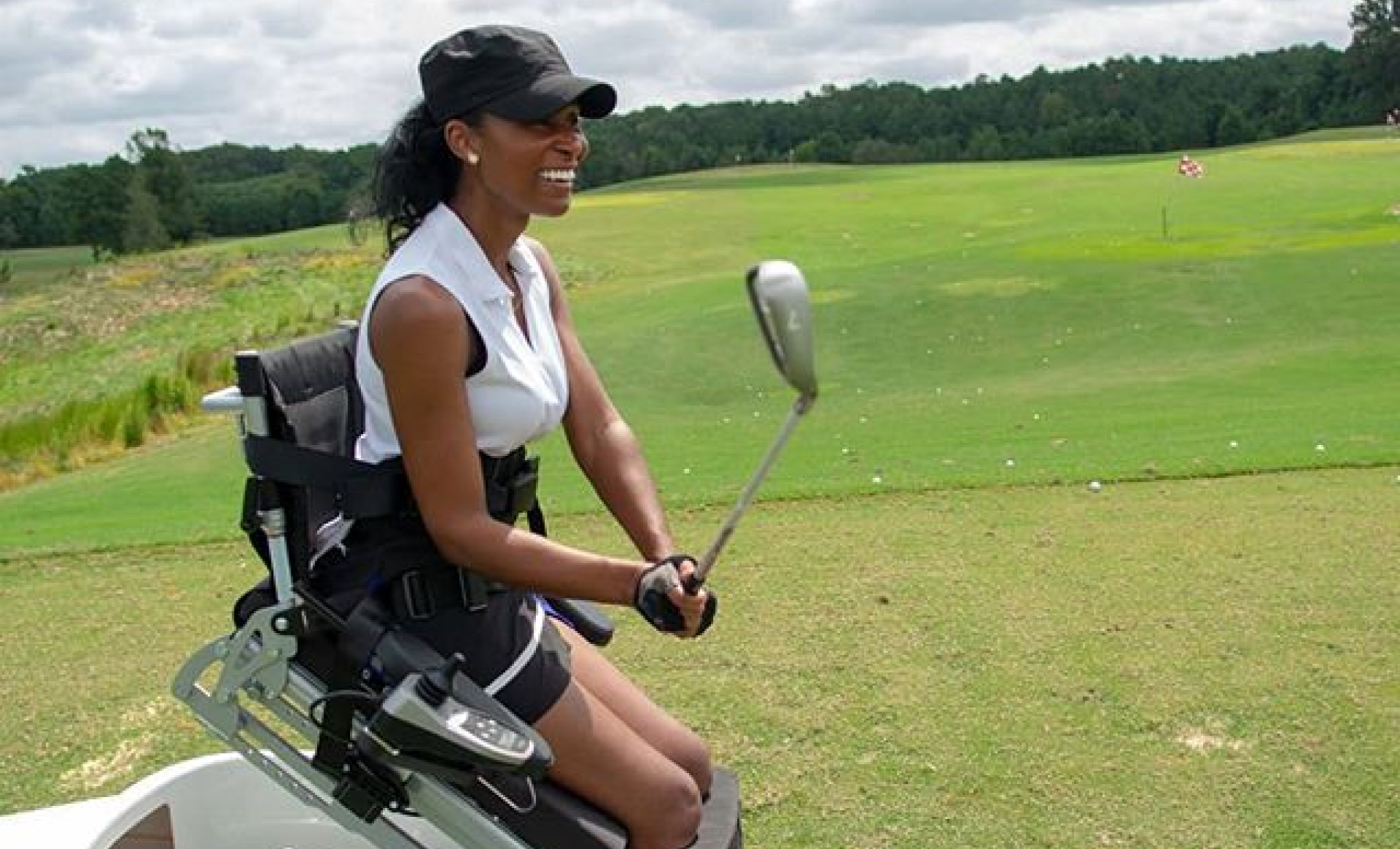 Tae McKenzie on golf course with assistive equipment on wheels holding golf club.