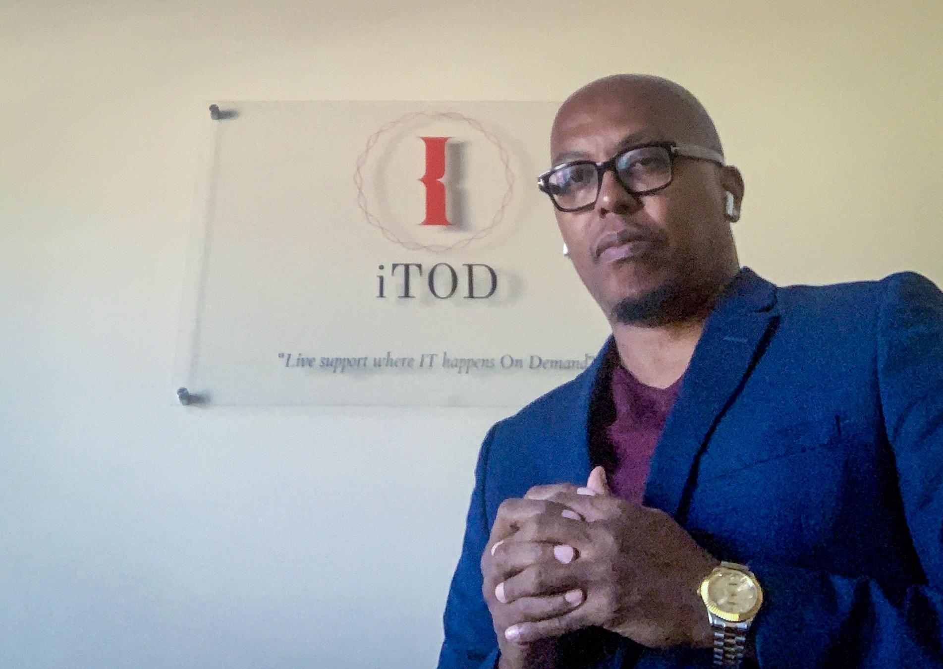 CEO Dorian Nimmons standing in front of corporate logo
