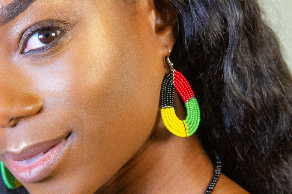 Model wearing a four-color bead earring with one eye visible
