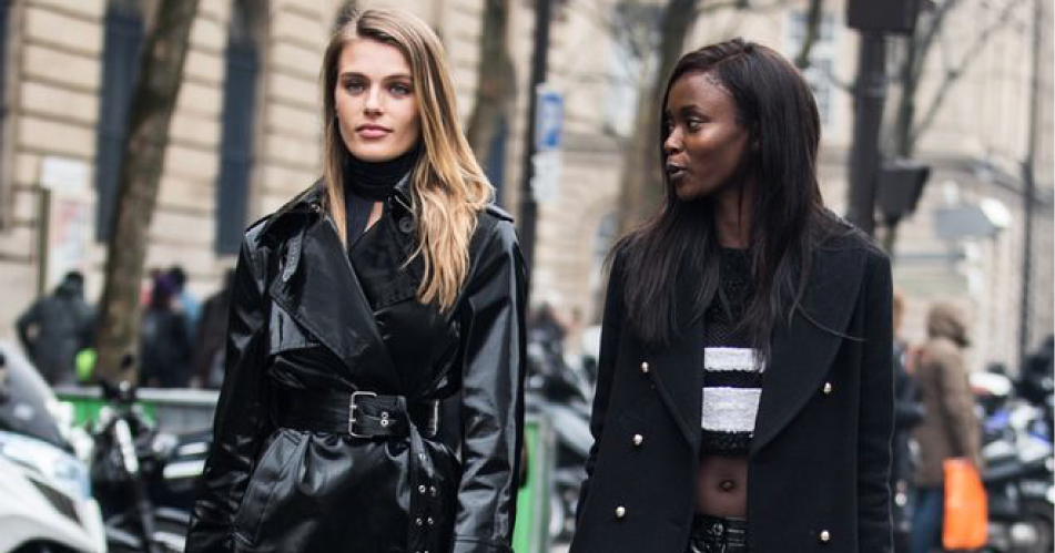 Two fashion models walking on the street with coats.