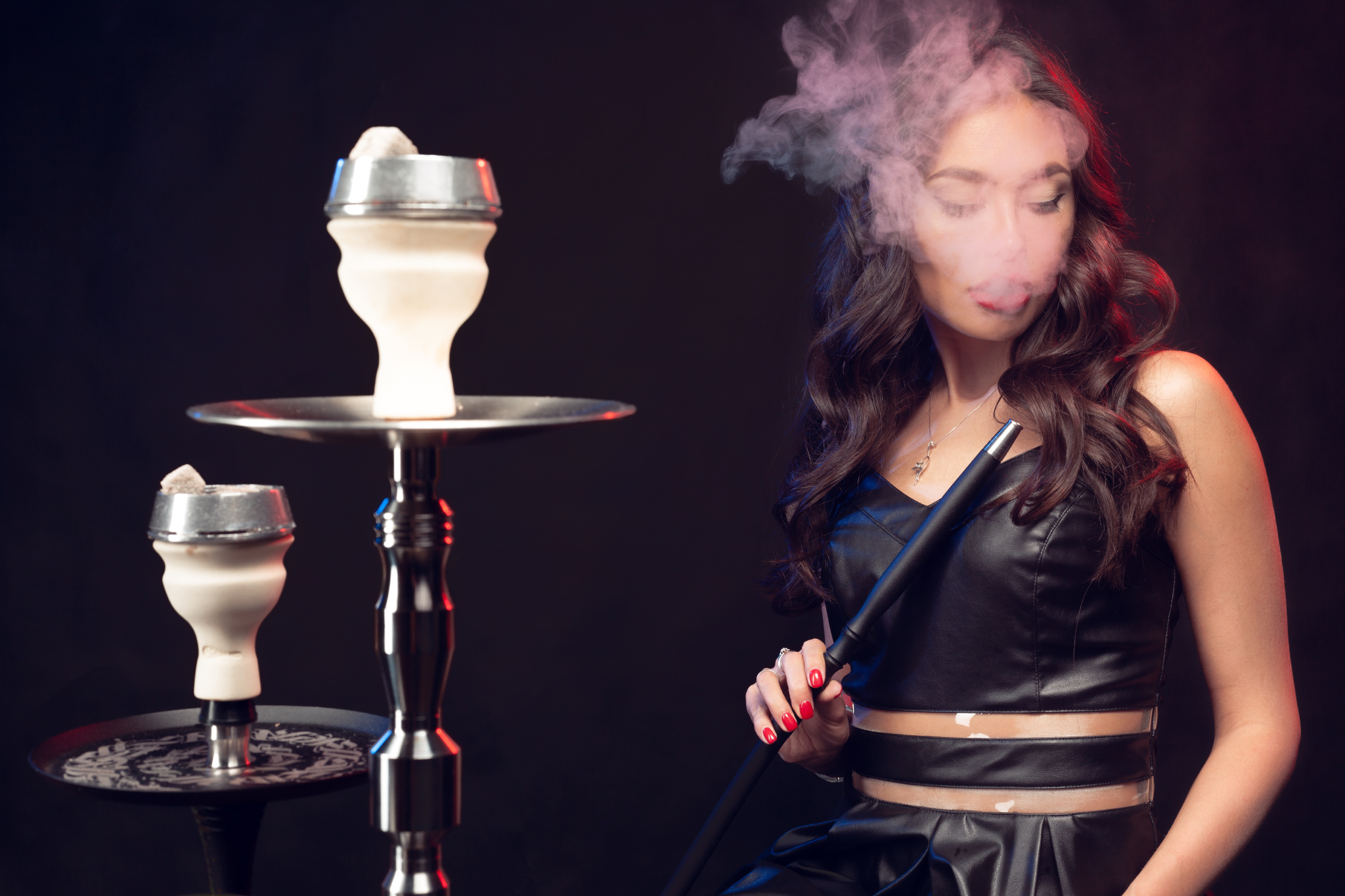 Woman exhaling smoke from hookah with black background.