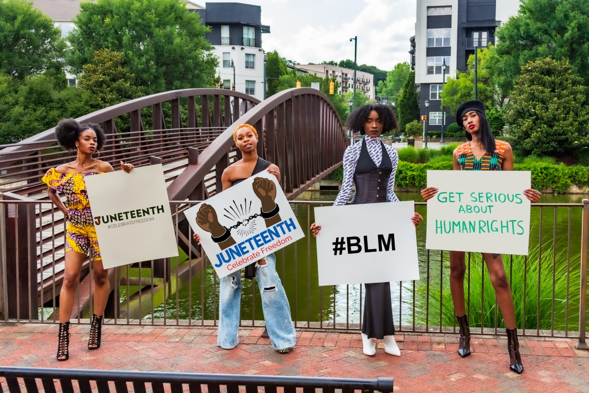 Juneteenth Advocates holding signs with Juneteenth, BLM, and Human Rights signs in front of bridge