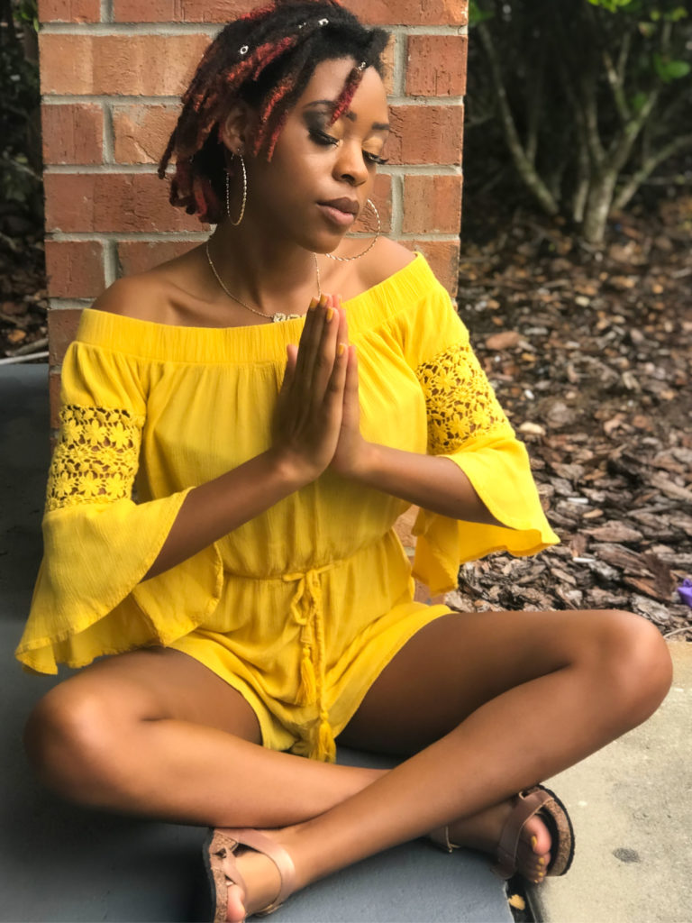 Young woman on the ground meditating with her hands clasped together.