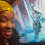 Symone in front of her Game PC with Apex Legends in the background on a computer screen